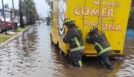 Dos bomberos apoyan para destapar coladeras y reestablecer vialidad tras encharcamiento en Avenida Tláhuac.