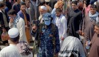 n miembro de las fuerzas de seguridad talibanes monta guardia entre las multitudes de personas que pasan por una calle en Kabul, Afganistán