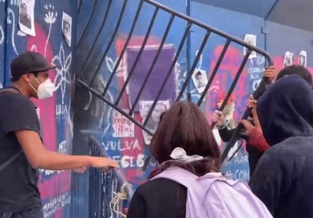 Hombres en la marcha intentando abrir las vallas en torno a Palacio Nacional.