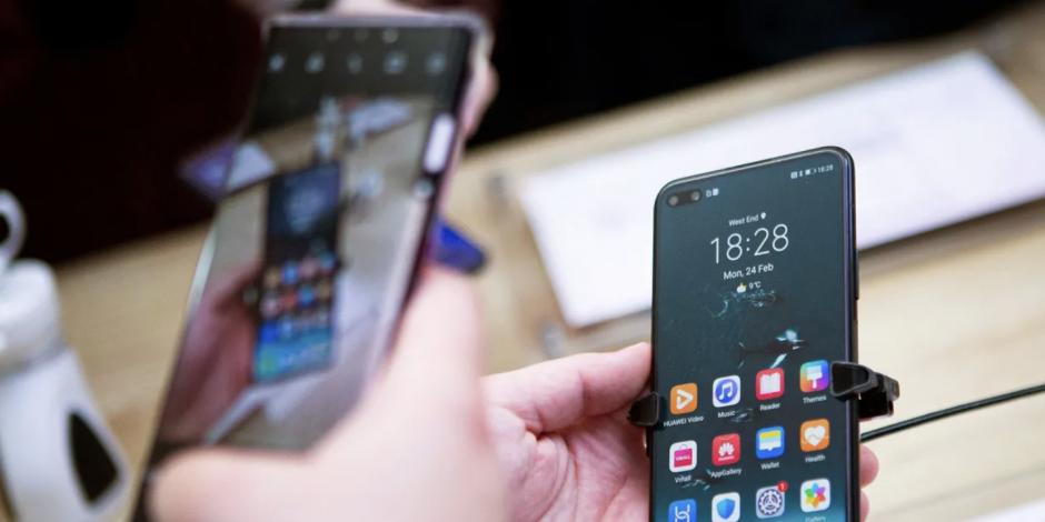 Dos personas manipulan dos teléfonos móviles