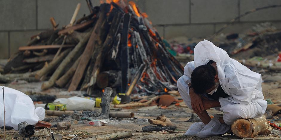 Un hombre llora junto a la pira ardiente de un familiar que murió por Covid-19, durante su cremación, en Nueva Delhi, el pasado 7 de mayo.