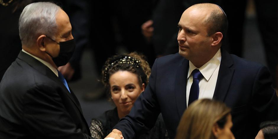 Naftali Bennett (der.) saluda a su exlíder Benjamin Netanyahu en el parlamento israelí, al concretar el cambio de poder, ayer.