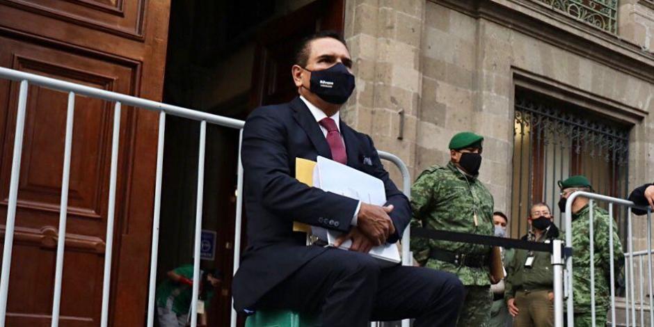 Silvano Aureoles, con más de una hora de espera, sentado afuera de Palacio Nacional, este martes.