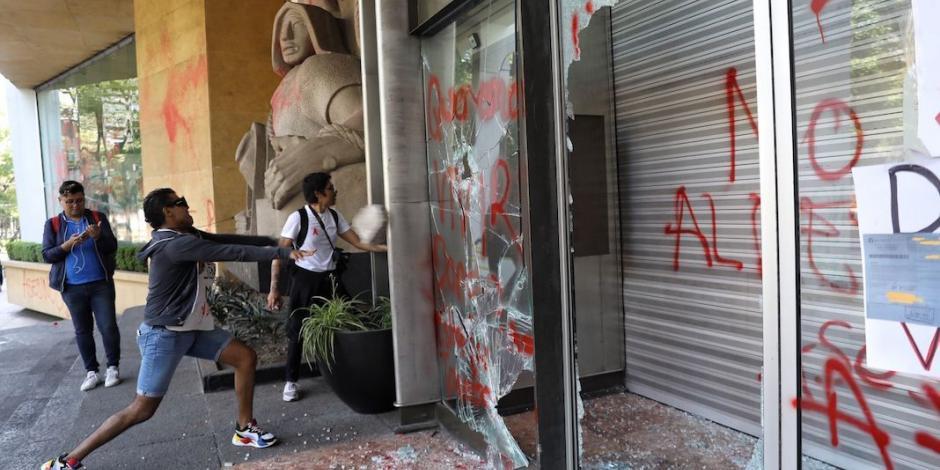Pintan esculturas y rompen puerta del IMSS; reclaman antirretrovirales