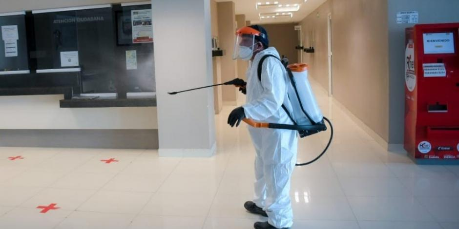 Un trabajador del municipio de Pedras Negras, Coahuila, sanitiza un espacio público
