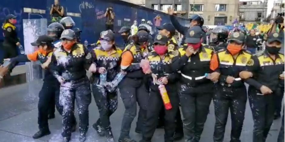 Manifestantes arrojan pintura a policías que les cierran paso al Zócalo