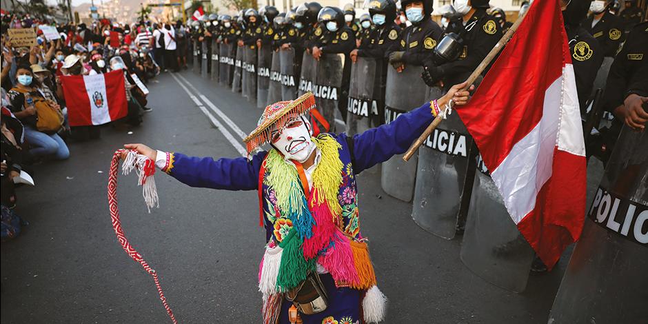 Artistas actúan junta a una línea policial el domingo afuera del Congreso.