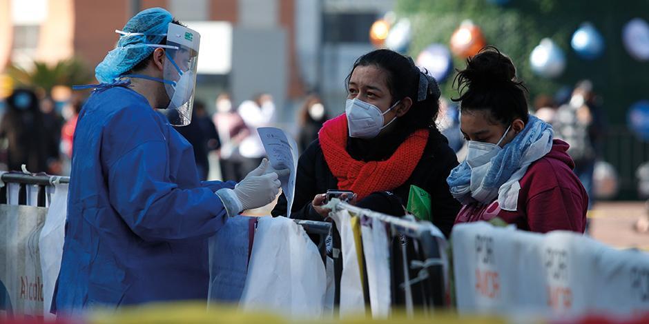 Un médico entrega los resultados de una prueba de Covid-19 a una mujer en un kiosco de salud, el sábado.