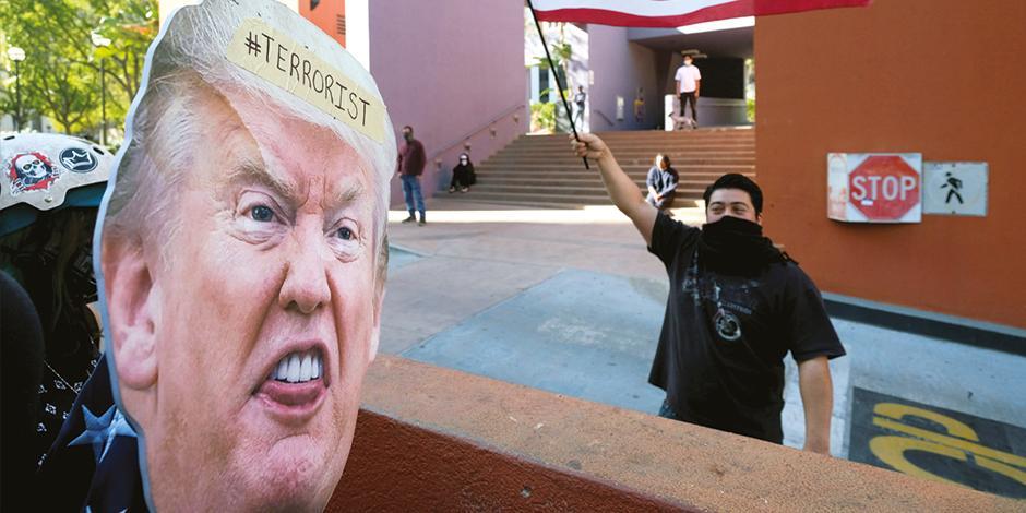 Un partidario del magnate sostiene una bandera frente a manifestantes anti-Trump en el centro de  Los Ángeles, ayer.