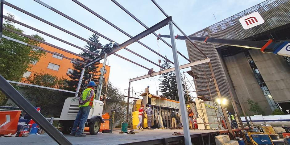 Trabajadores del Metro y de la CFE construyen la nueva matriz del STC, afuera del edificio incendiado, ayer.