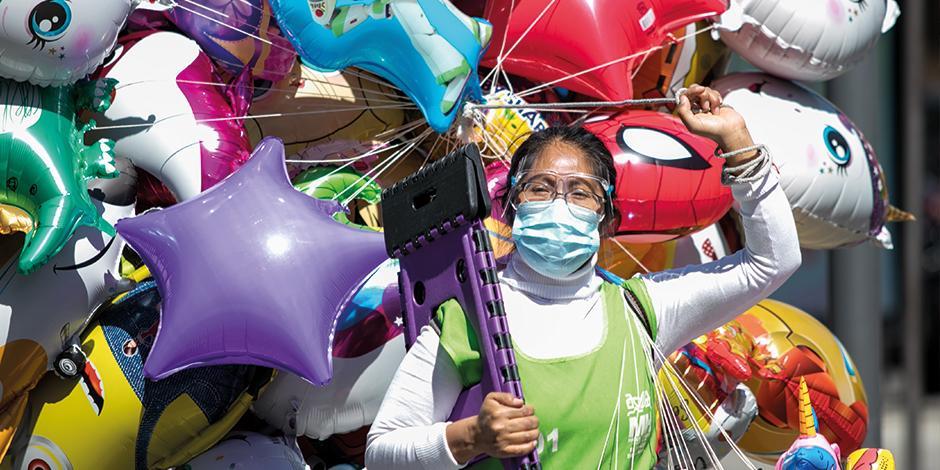 Una vendedora de globos intenta sacar el día con paseantes dominicales en la zona de Polanco, ayer.