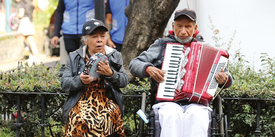 La pareja de adultos canta en un parque de la CDMX para ganar dinero, ayer.