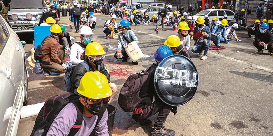 Manifestantes se cubren la cabeza con cascos ante la fuerza excesiva, ayer.