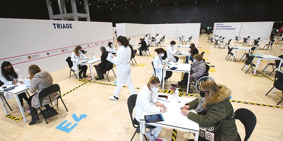 Personal sanitario aplica dosis en un centro de convenciones de Roma, Italia, ayer.