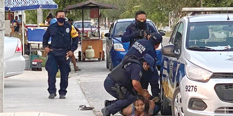uniformados someten contra el asfalto a la víctima, el sábado.