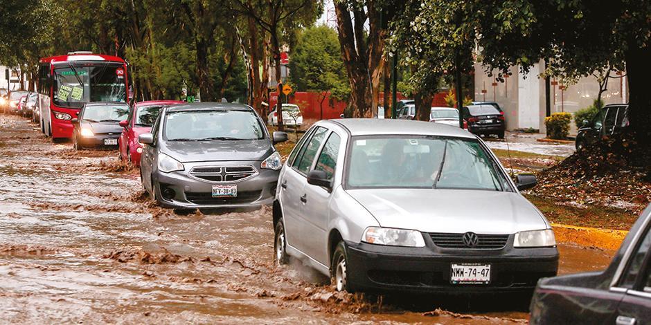 Automóviles transitan en una calle anegada, en el centro de Metepec, ayer.