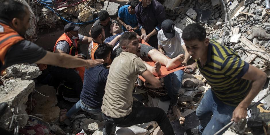 Palestinos ayudan, ayer, a víctimas en un edificio derrumbado en Gaza.