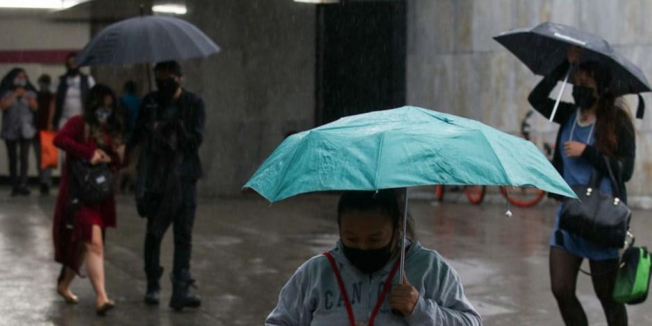 Personas con paraguas que salen la estación Insurgentes del Metro capitalino.