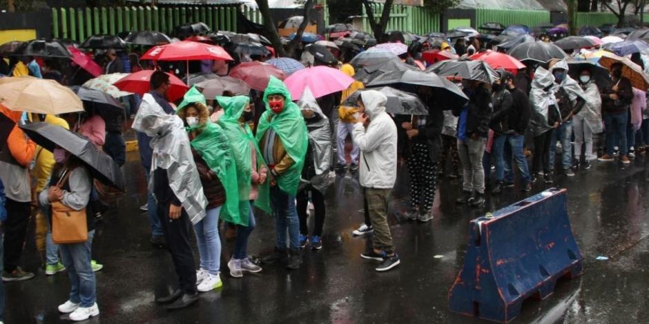 Bajo la lluvia, jóvenes y persona rezagadas abarrotan el Deportivo Xochimilco para la vacunación contra COVID-19.