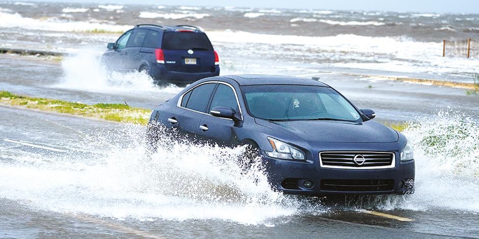 """Automovilistas """"navegan"""" en avenidas inundadas, ayer."""