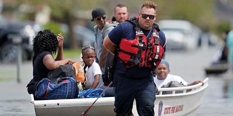 Rescatistas ayudan con lanchas a la población afectada en vecindarios de Louisiana, ayer.